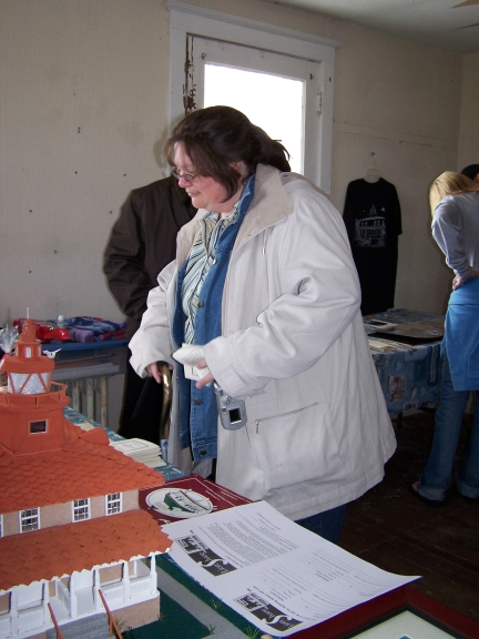 A visitor browses the PLLPS merchandise table